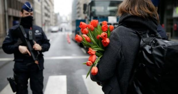 Une femme arrive avec des fleurs à la station de métro de Maelbeek le 23 mars 2016 à Bruxelles. (Photo : AFP)