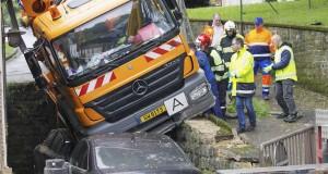 """Les deux voitures stationnées en contrebas ont """"amorti"""" la chute du camion-citerne. (Photo Jean-Claude Ernst)"""
