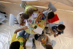 Assis à une petite table, plusieurs enfants âgés de 4 et 8 ans sortent une boîte de crayons de couleurs et se mettent à raconter le drame vécu en images. (Photos AP)