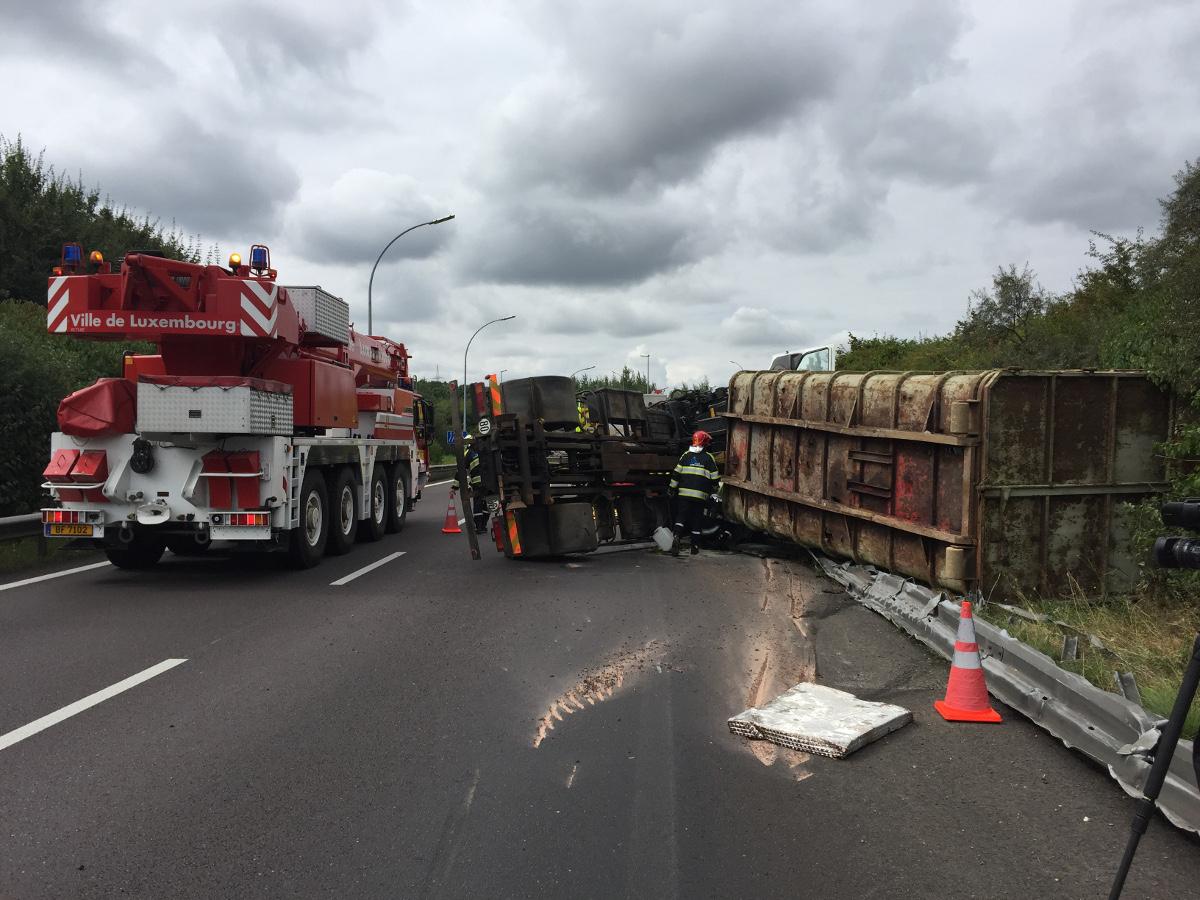 Le camion s'est renversé en partie sur les glissières de sécurité. Le passager doit être désincarcéré à l'aide de plusieurs grues. (photo police grand-ducale)
