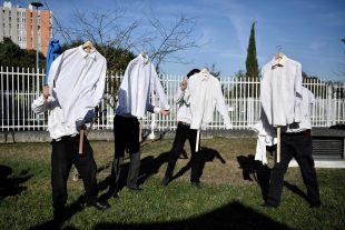 """Des manifestants ont réalisé une performance autour de """"l'affaire de la chemise"""", en soutien aux salariés jugés. (Photos AP)"""